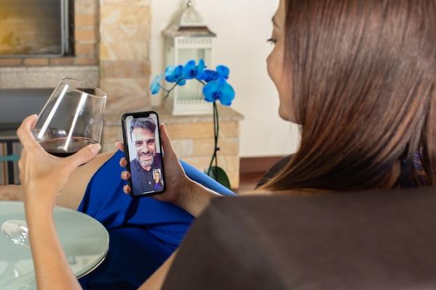 La donna parla con un amico in videochiamata seduta nel suo salotto