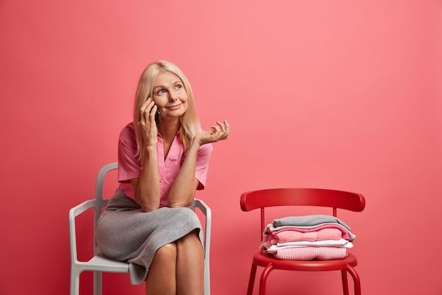 La donna parla tramite telefono cellulare ha un'espressione sognante vestita con abiti casual posa sulla sedia in rosa