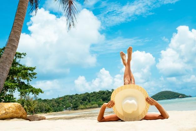 Concia della donna che si distende sulla spiaggia. femmina adulta dalla parte posteriore sdraiata con cappello di paglia a prendere il sole sotto il sole tropicale