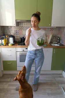 La donna assaggia con il suo dito la salsa di pesto aromatica montata nel frullatore vyzsla cane che elemosina il cibo