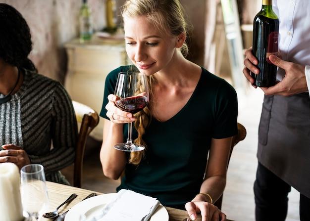 Donna che assaggia vino rosso in un ristorante di classe