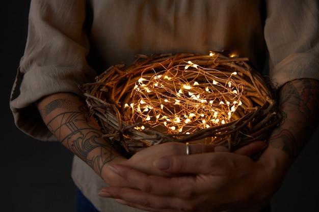 Mani del tatuaggio della donna che tengono il nido con le luci di natale