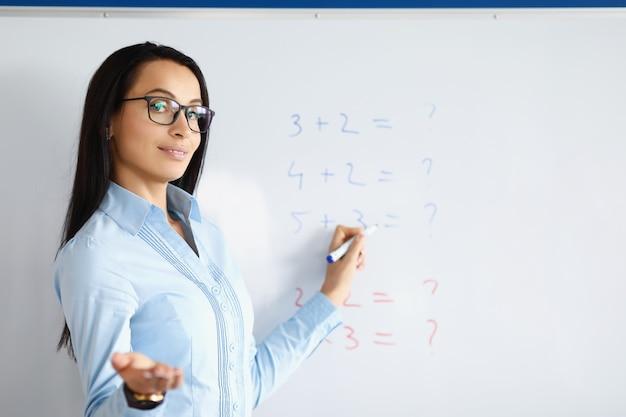 Insegnante donna in piedi alla lavagna con formule e spiegando informazioni