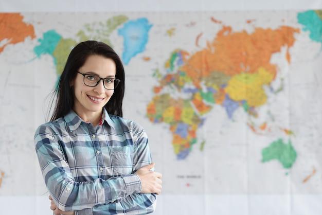 Insegnante donna con gli occhiali in piedi sullo sfondo della mappa del mondo