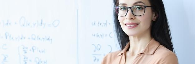 Insegnante donna con gli occhiali si trova vicino a una lavagna bianca