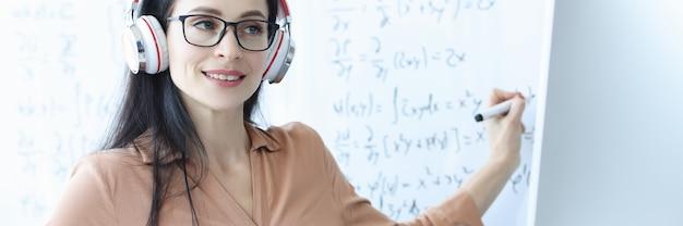 Insegnante donna con cuffie conduce lezioni di matematica online