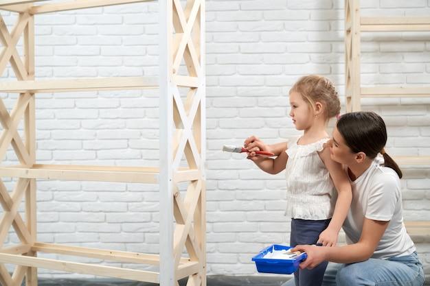 Donna che insegna alla sua bella figlia a dipingere con il pennello
