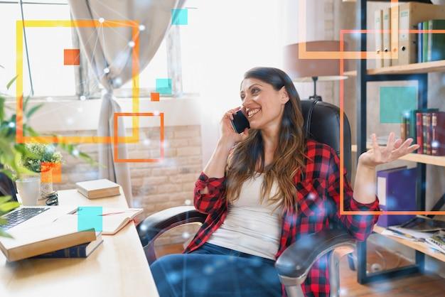 Telelavoratore donna lavora a casa con un laptop e uno smartphone