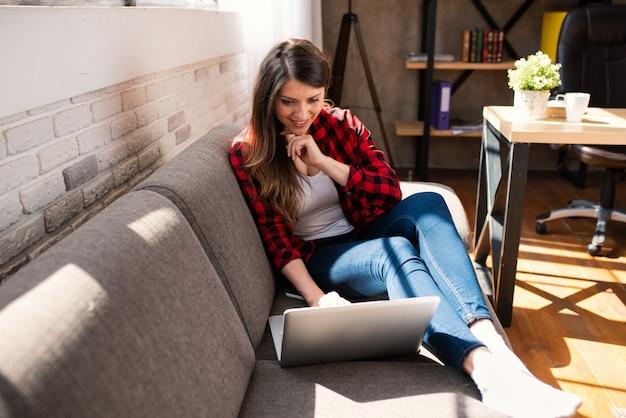 Telelavoratore donna lavora a casa con un laptop.