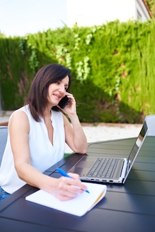 Una donna che telelavora fuori con il suo laptop e parla al cellulare mentre prende appunti su un taccuino