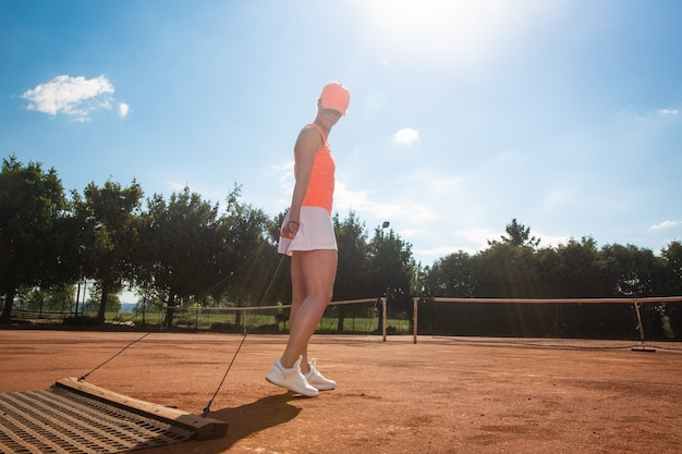 Giocatore di tennis della donna che prepara un campo da tennis prima della sua partita