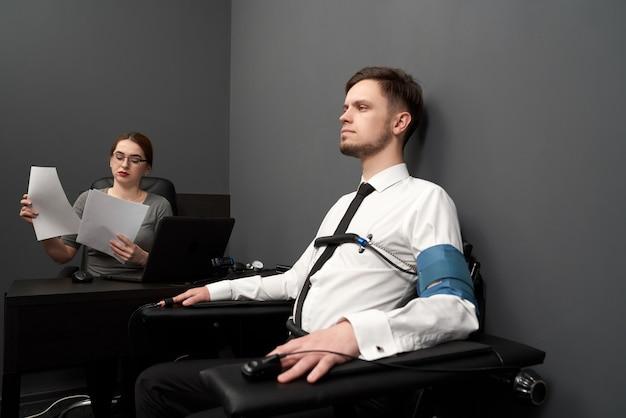 Uomo di prova della donna con il poligrafo nella stanza grigia.