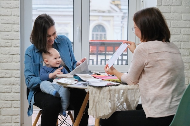 Designer tessile donna e giovane madre con bambino che sceglie tessuti per tende, cuscini, copriletti, tappezzeria