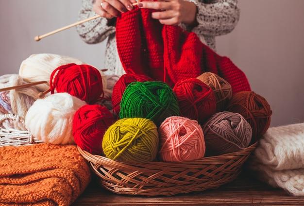 La donna che tiene gli aghi e lavora a maglia una giacca calda rossa sul mercato