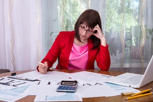 Donna che pensa a 1040 modulo fiscale in ufficio