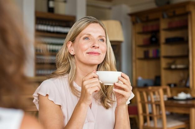 Donna che pensa sopra il caffè