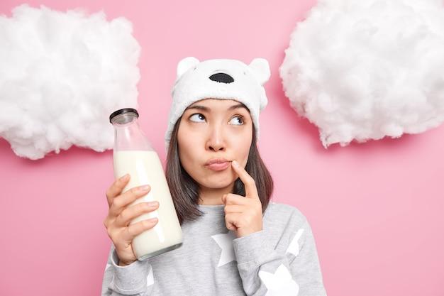 La donna pensa a cosa cucinare dal latte tiene il dito all'angolo della bocca concentrato verso l'alto vestita con abiti domestici casuali
