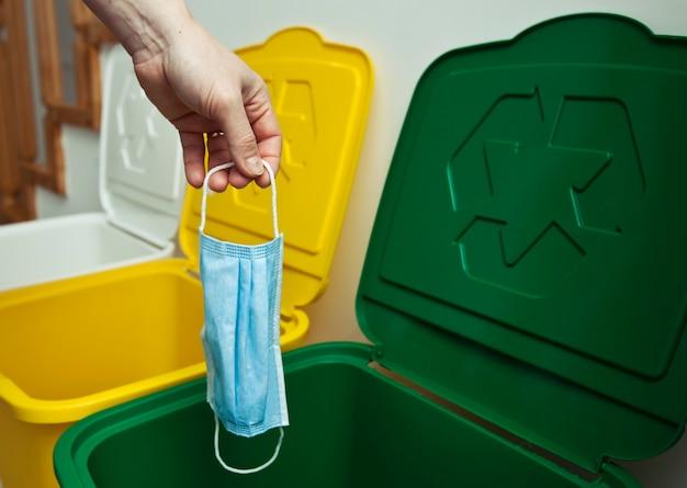 La donna che lancia la mascherina medica in uno dei tre bidoni della spazzatura