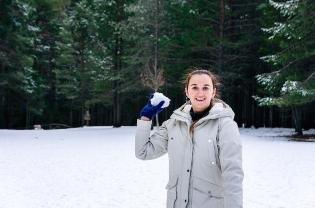 Donna che lancia palle di neve in un paesaggio innevato naturale.