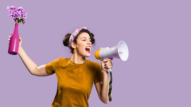 Donna che getta un vaso con fiori e grida in megafono