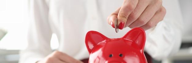 La donna getta la moneta nel concetto di rifornimento del conto di investimento del porcellino salvadanaio