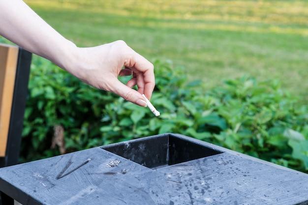 La donna getta il mozzicone di sigaretta in un bidone della spazzatura di metallo in un parco cittadino. primo piano di una mano femminile.