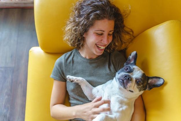 Bulldog solletico donna a casa sul divano. vista dall'alto orizzontale della donna che gioca con l'animale domestico