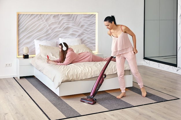 La donna riordina la camera da letto con l'aspirapolvere mentre sua figlia ascolta la musica sullo smartphone tramite le cuffie mentre è sdraiata a pancia in giù a letto.