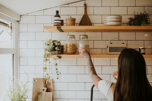 Donna che riordina la dispensa della parete della cucina