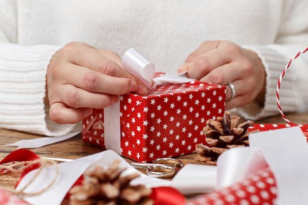 La donna lega un fiocco di nastro su un regalo avvolto
