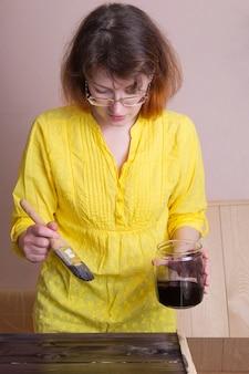 Una donna tinta in una tavola legnosa scura. lavoro creativo in officina. fatto a mano su legno