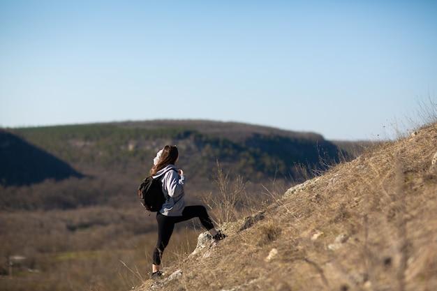 Donna in cima a una scogliera di montagna con una bellissima natura
