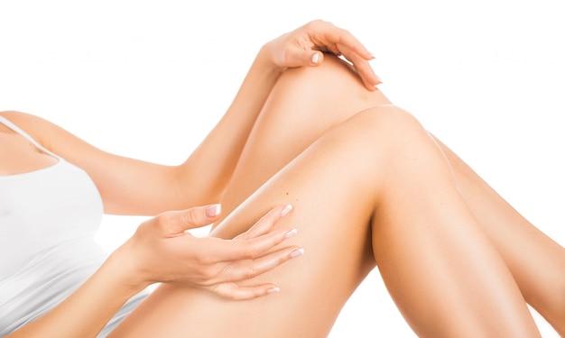Donna toccando la gamba con una pelle luminosa perfetta. concetto di cura della pelle. isolato su bianco