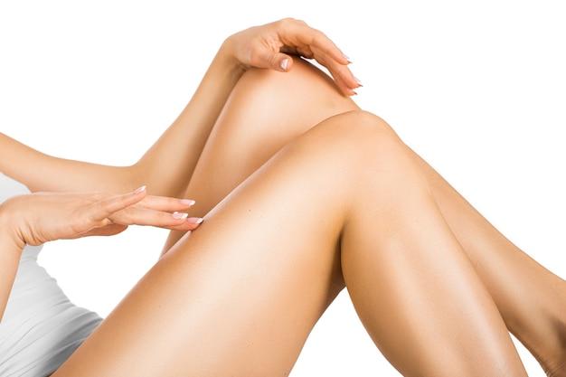 Donna toccando la gamba con una pelle luminosa perfetta. concetto di cura della pelle.