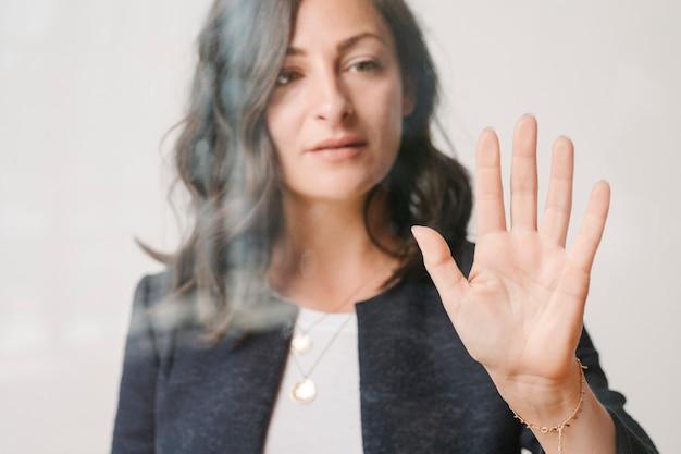 Donna che tocca uno schermo con il palmo