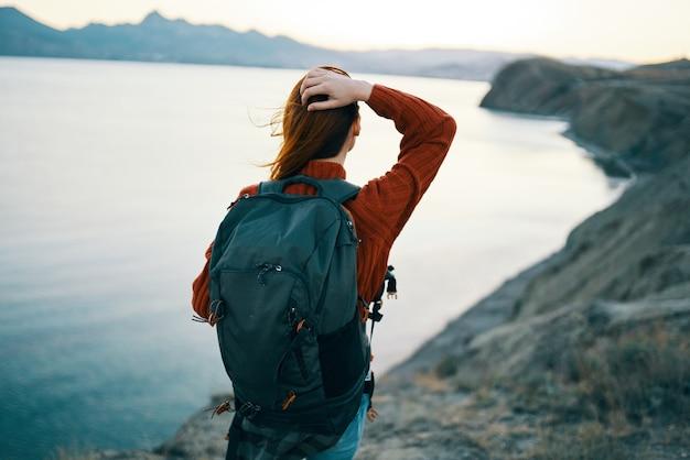 Zaino turistico della donna nella natura attiva di viaggio di svago delle montagne. foto di alta qualità