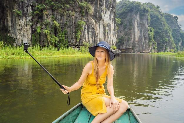 Turista in barca sul lago tam coc ninh binh viet nam è sito patrimonio mondiale dell'unesco