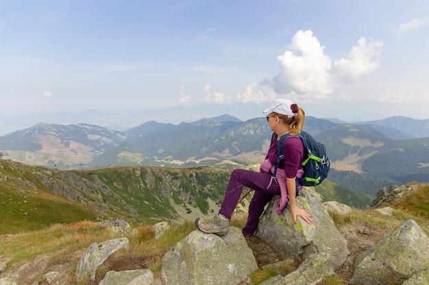 La donna in abiti da turista guarda in lontananza tra le montagne. alti tatra. slovacchia.