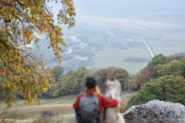 Turista della donna accanto a un cane nel paesaggio di viaggio di montagna