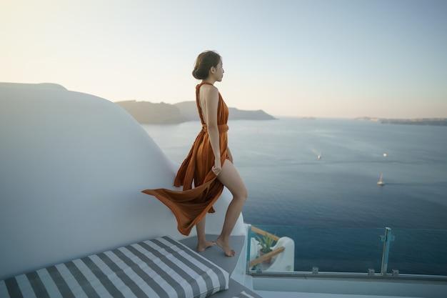 Turista della donna in vestito splendido che visita il villaggio imbiancato a oia santorini grecia