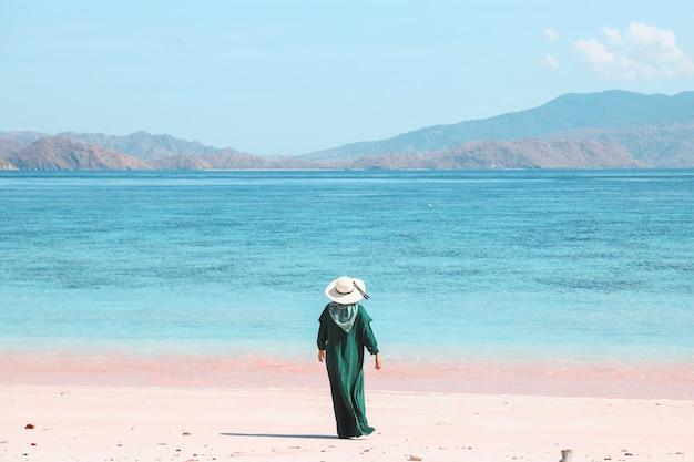 Turista in abito verde e cappello estivo in piedi sulla spiaggia di sabbia rosa che si gode a labuan bajo