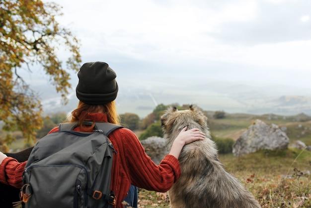 Turista della donna abbraccia un cane in natura ammira il paesaggio