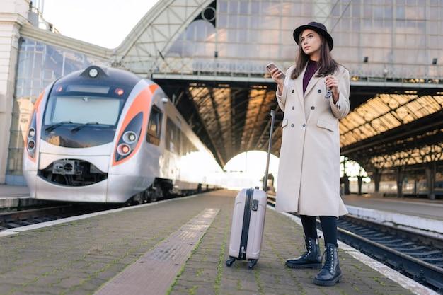 Turista della donna sulla piattaforma della stazione ferroviaria