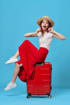 Donna turista valigia rossa vacanza divertimento occhiali da sole travel