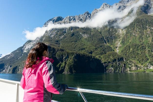 Turista della donna sulla piattaforma della nave in milford sound