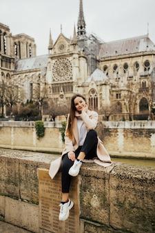 Donna turistica seduta davanti alla famosa cattedrale di notre dame a parigi.