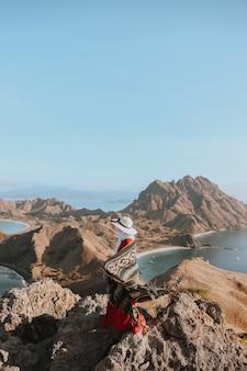 Turista in cappello estivo godendo la vacanza sulla collina superiore a padar island labuan bajo