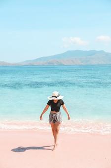 Turista in cappello estivo che cammina sulla spiaggia di sabbia rosa con vista mare e colline a labuan bajo