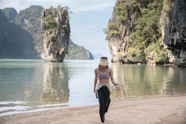 Turista in costume da bagno in posa sull'isola di james bond, phang nga, thailandia.