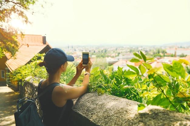 Turista scatta una foto vista panoramica con i tetti rossi di lubiana dal castello su smart phone